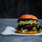 Delicious vegan Red Beet, White Bean &Quinoa Burger with Avocado on a pillowy turmeric brioche bun