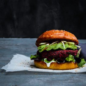 Delicious vegan Red Beet, White Bean &Quinoa Burger with Avocado on a pillowy turmeric brioche bun