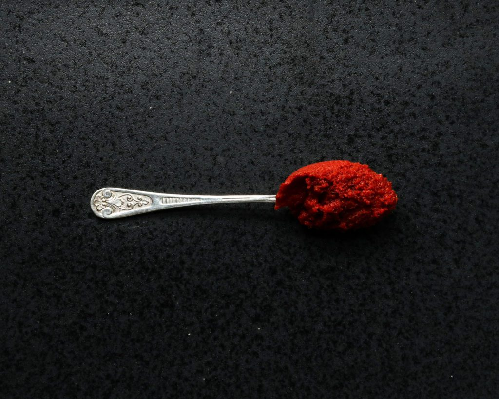 silver spoon with red curry paste on a dark stone underground