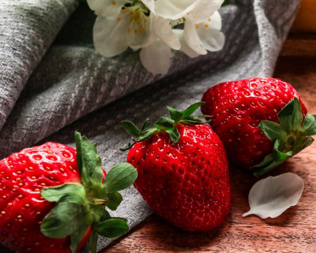 3 Strawberries on an wooden underground, grey linen, flowers