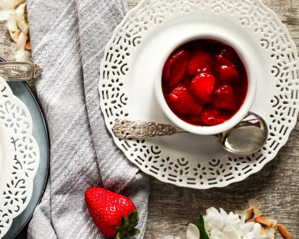 Strawberry Compote in a small white pot on a white plate with a spoon
