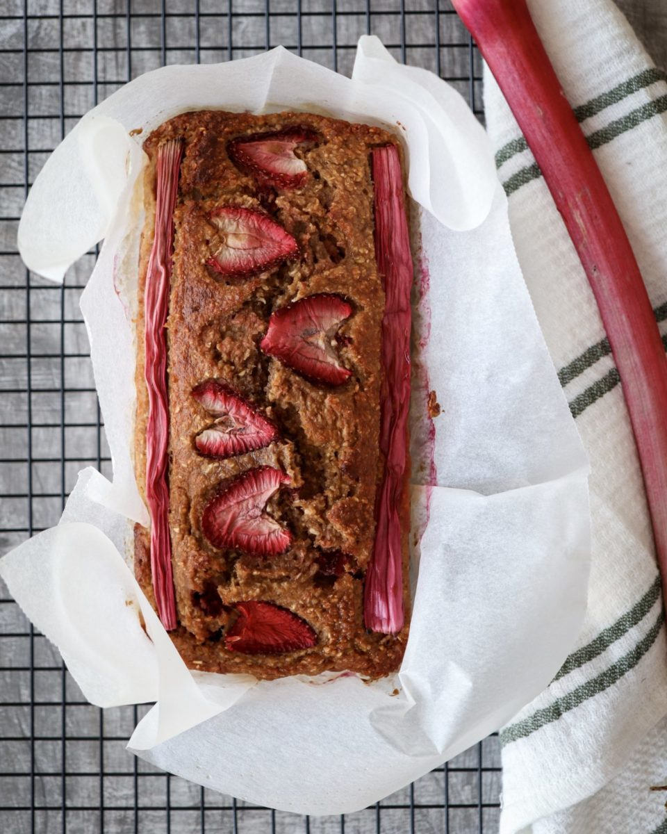 Banana Bread with strawberries placed on a white green striped kitchen towel with rhubarb.