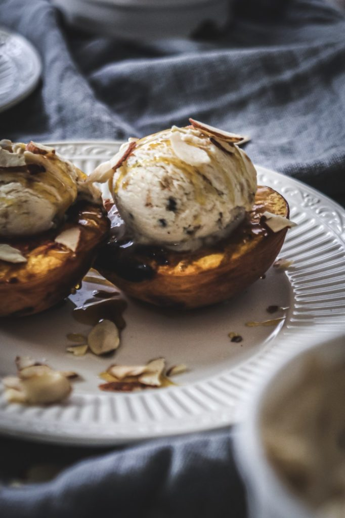 grilled peaches with ice cream on white plate