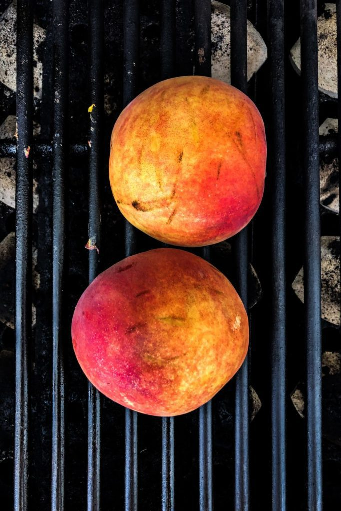 two peaches halves on the grill