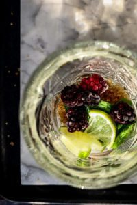 glas from above with blackberries, mint leaves, lime slices and brown sugar