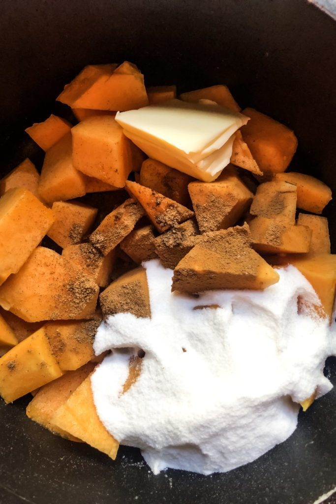 pumpkin chunks, sugar, and spices in a black pot