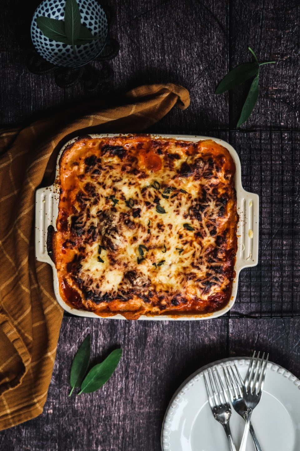 Kohlrabi lasagna casserole with blight brown linen and plates and forks on either side