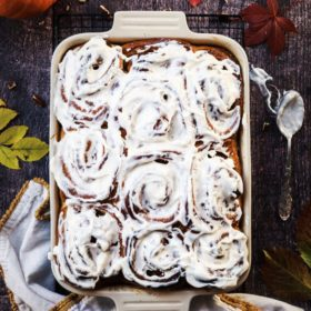 cinnamon brioche rolls in a baking sheet with autumnally decoration